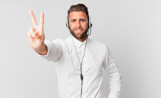 Jonge knappe man die lacht en er vriendelijk uitziet, met nummer twee. telemarketing concept