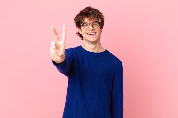 Jonge knappe man die lacht en er vriendelijk uitziet, met nummer twee