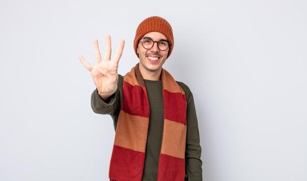 Jonge knappe man die lacht en er vriendelijk uitziet, met nummer vier. winterkleren concept