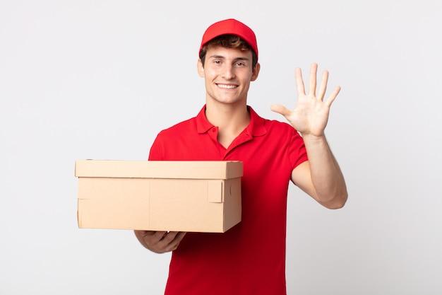 Jonge knappe man die lacht en er vriendelijk uitziet, met nummer vijf leveringspakketserviceconcept.