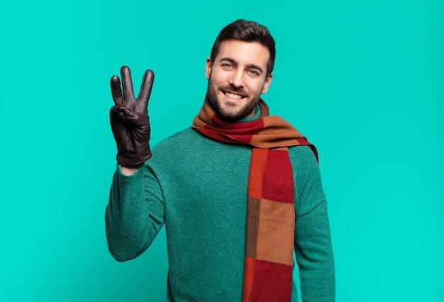 Jonge knappe man die lacht en er vriendelijk uitziet, nummer drie of derde toont met de hand naar voren, aftellend. koud en winterconcept