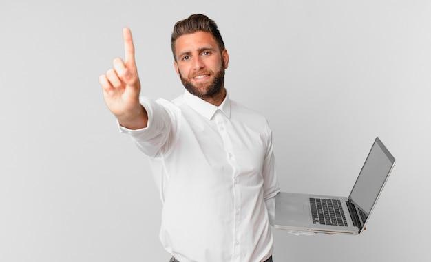 Jonge knappe man die lacht en er vriendelijk uitziet, nummer één toont en een laptop vasthoudt