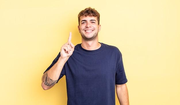 Jonge knappe man die lacht en er vriendelijk uitziet, nummer één toont of als eerste met de hand naar voren, aftellend