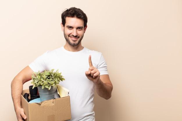 Jonge knappe man die lacht en er vriendelijk uitziet, nummer één toont of eerst met de hand naar voren Premium Foto