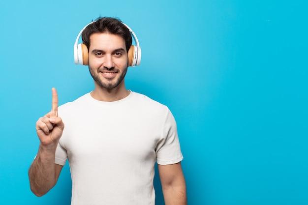 Jonge knappe man die lacht en er vriendelijk uitziet, nummer één toont of eerst met de hand naar voren