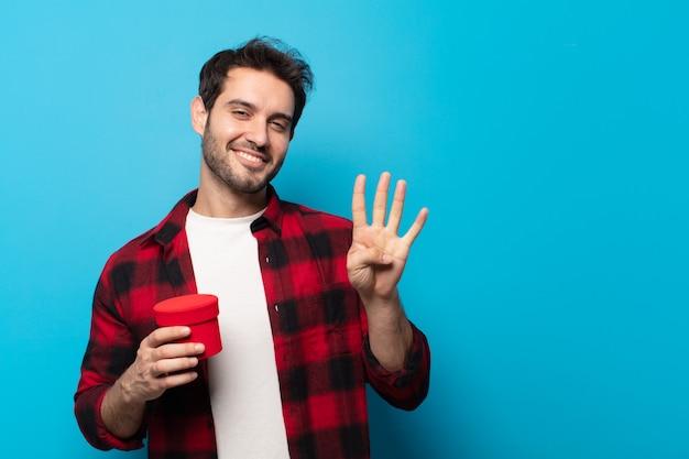 Jonge knappe man die lacht en er vriendelijk uitziet, nummer vier of vierde toont met de hand naar voren, aftellend