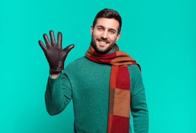 Jonge knappe man die lacht en er vriendelijk uitziet, nummer vijf of vijfde toont met de hand naar voren, aftellend