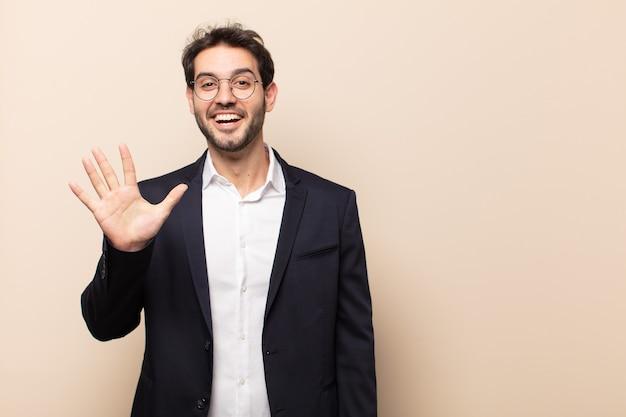 Jonge knappe man die lacht en er vriendelijk uitziet, nummer vijf of vijfde toont met de hand naar voren