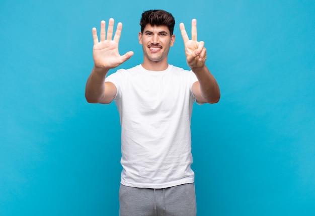 Jonge knappe man die lacht en er vriendelijk uitziet, nummer zeven of zevende toont met de hand naar voren, aftellend