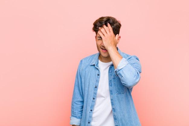 """Jonge knappe man die lacht en op zijn voorhoofd slaat als dã ¢ â € âšãƒâ """"ãƒâ´oh! ik was het vergeten of dat was een domme fout tegen een roze achtergrond"""