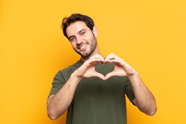 Jonge knappe man die lacht en zich gelukkig, schattig, romantisch en verliefd voelt, en met beide handen hartvorm maakt