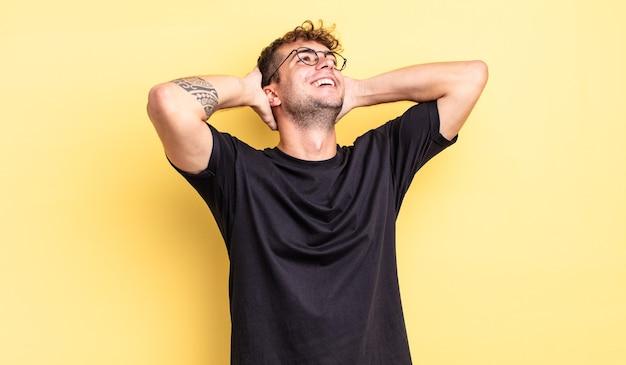 Jonge knappe man die lacht en zich ontspannen, tevreden en zorgeloos voelt, positief lacht en chillt