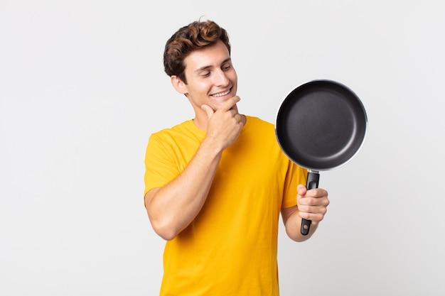 Jonge knappe man die lacht met een gelukkige, zelfverzekerde uitdrukking met de hand op de kin en een kookpan vasthoudt
