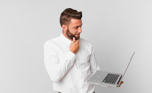 Jonge knappe man die lacht met een gelukkige, zelfverzekerde uitdrukking met de hand op de kin en een laptop vasthoudt