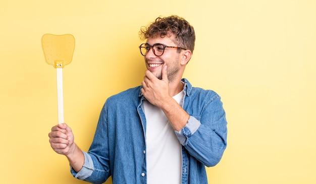 Jonge knappe man die lacht met een gelukkige, zelfverzekerde uitdrukking met de hand op de kin. vliegenmepper concept