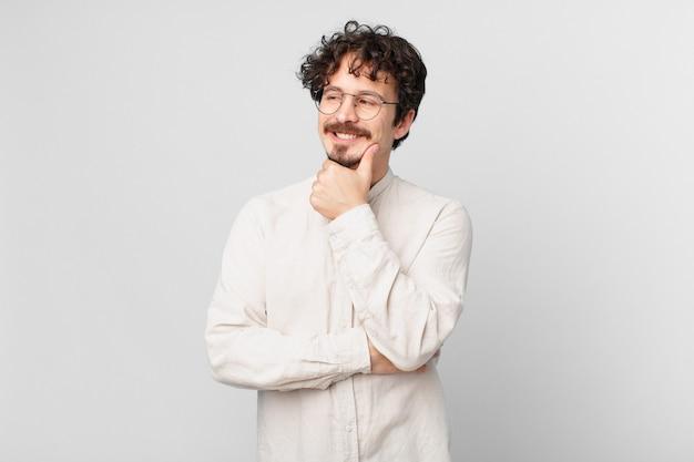 Jonge knappe man die lacht met een gelukkige, zelfverzekerde uitdrukking met de hand op de kin