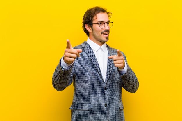 Jonge knappe man die lacht met een positieve, succesvolle, gelukkige houding wijzend naar de camera, waardoor pistool ondertekenen met handen op oranje muur