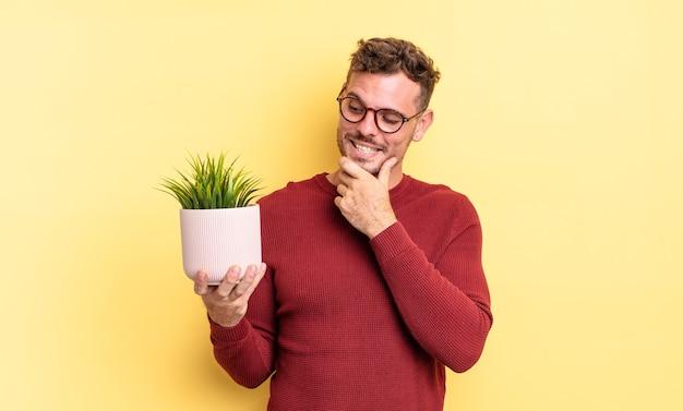 Jonge knappe man die lacht met een vrolijke, zelfverzekerde uitdrukking met de hand op de kin. decoratief plantenconcept