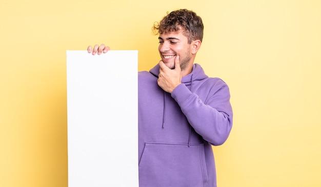 Jonge knappe man die lacht met een vrolijke, zelfverzekerde uitdrukking met de hand op de kin. kopieer ruimteconcept