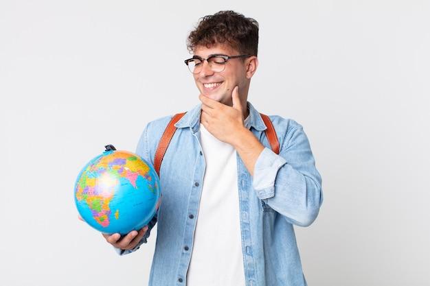 Jonge knappe man die lacht met een vrolijke, zelfverzekerde uitdrukking met de hand op de kin. student met een wereldbolkaart