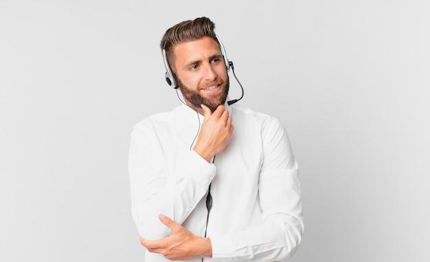 Jonge knappe man die lacht met een vrolijke, zelfverzekerde uitdrukking met de hand op de kin. telemarketing concept