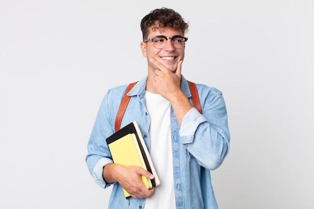 Jonge knappe man die lacht met een vrolijke, zelfverzekerde uitdrukking met de hand op de kin. universitair studentenconcept