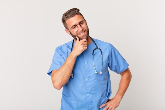 Jonge knappe man die lacht met een vrolijke, zelfverzekerde uitdrukking met de hand op de kin. verpleegster concept