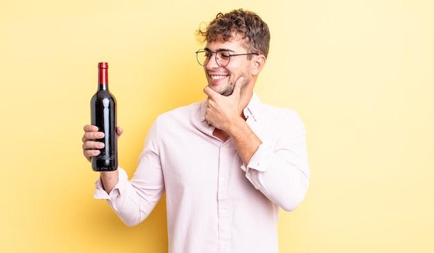 Jonge knappe man die lacht met een vrolijke, zelfverzekerde uitdrukking met de hand op de kin. wijnfles concept