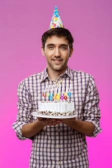 Jonge knappe man die lacht, verjaardagstaart houden over paarse muur.