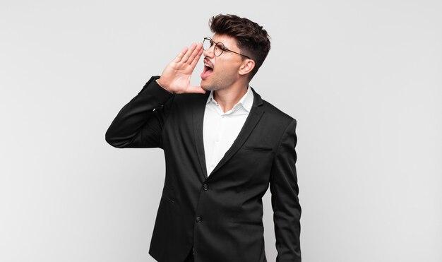 Jonge knappe man die luid en boos schreeuwt om ruimte aan de zijkant te kopiëren, met de hand naast de mond