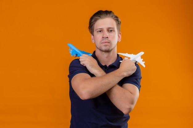 Jonge knappe man die met gekruiste armen bedrijf speelgoed vliegtuigen camera kijken met droevige uitdrukking ongelukkig zonder glimlach op oranje achtergrond