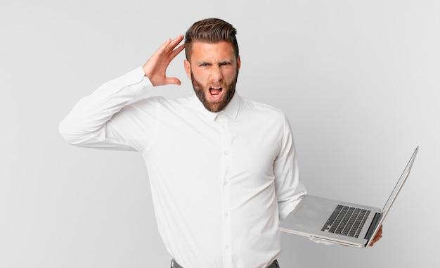 Jonge knappe man die met zijn handen in de lucht schreeuwt en een laptop vasthoudt