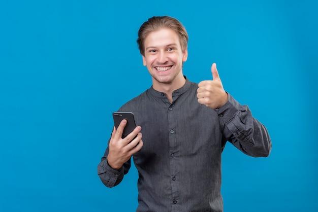 Jonge knappe man die mobiele telefoon houdt die duimen die omhoog glimlachen staande over blauwe muur houden