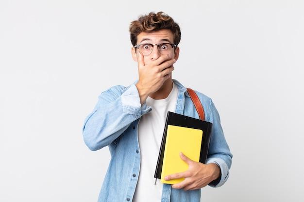 Jonge knappe man die mond bedekt met handen met een geschokt. universitair studentenconcept