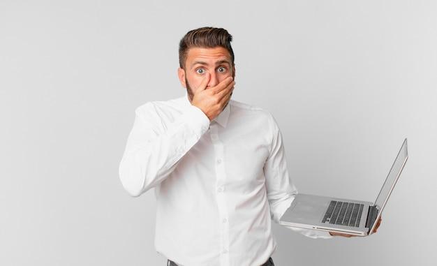 Jonge knappe man die mond bedekt met handen met een geschokte en een laptop vasthoudt