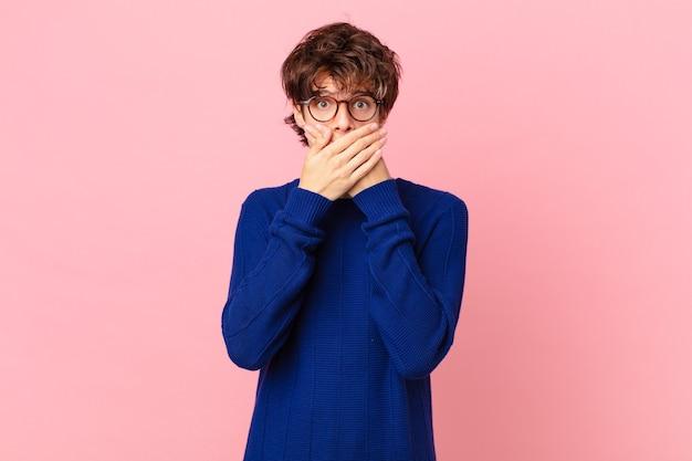 Jonge knappe man die mond bedekt met handen met een geschokte