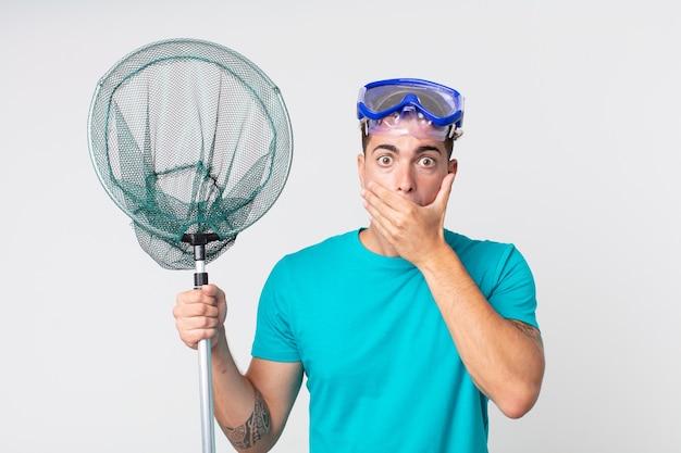 Jonge knappe man die mond bedekt met handen met een schok met bril en visnet