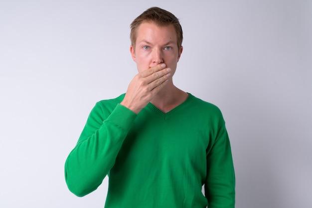 Jonge knappe man die mond behandelt als concept van drie wijze apen
