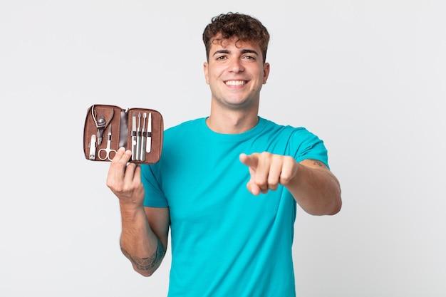 Jonge knappe man die naar de camera wijst en jou kiest en een spijkergereedschapskist vasthoudt