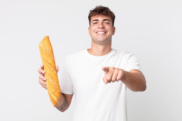 Jonge knappe man die naar de camera wijst en jou kiest en een stokbrood vasthoudt