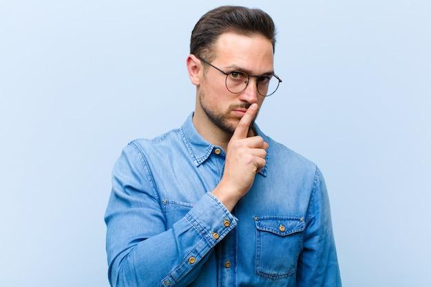 Jonge knappe man die om stilte en stilte vraagt, gebaart met vinger voor mond, shh zegt of een geheim bewaart