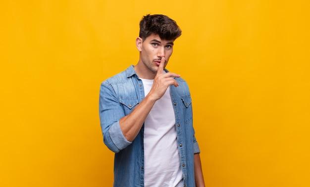 Jonge knappe man die om stilte en stilte vraagt, met de vinger voor de mond gebaart, shh zegt of een geheim bewaart