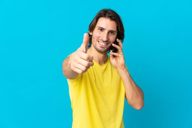 Jonge knappe man die op blauw wordt geïsoleerd en een gesprek met de mobiel houdt terwijl hij duimen omhoog doet
