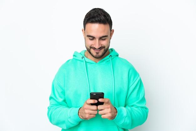 Jonge knappe man die op witte muur wordt geïsoleerd die een bericht of e-mail met mobiel verzendt