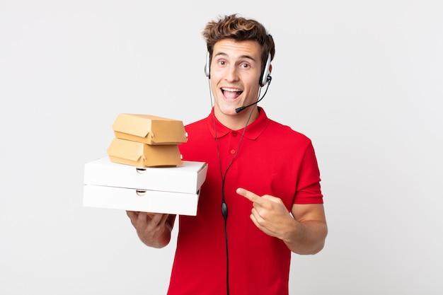 Jonge knappe man die opgewonden en verrast kijkt en naar de zijkant wijst. afhaal fastfood concept