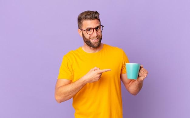 Jonge knappe man die opgewonden en verrast kijkt en naar de zijkant wijst. en een koffiemok vasthouden