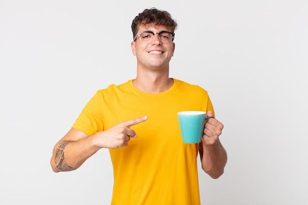Jonge knappe man die opgewonden en verrast kijkt en naar de zijkant wijst en een kopje koffie vasthoudt