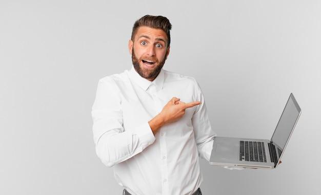 Jonge knappe man die opgewonden en verrast kijkt en naar de zijkant wijst en een laptop vasthoudt