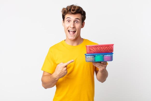 Jonge knappe man die opgewonden en verrast kijkt en naar de zijkant wijst en lunchboxen vasthoudt