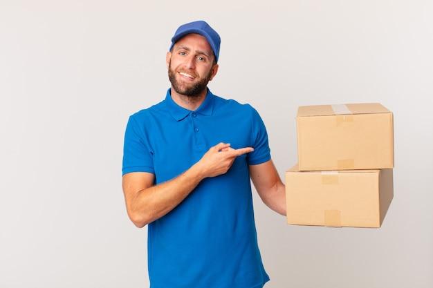 Jonge knappe man die opgewonden en verrast kijkt en naar de zijkant wijst. pakket leveren concept